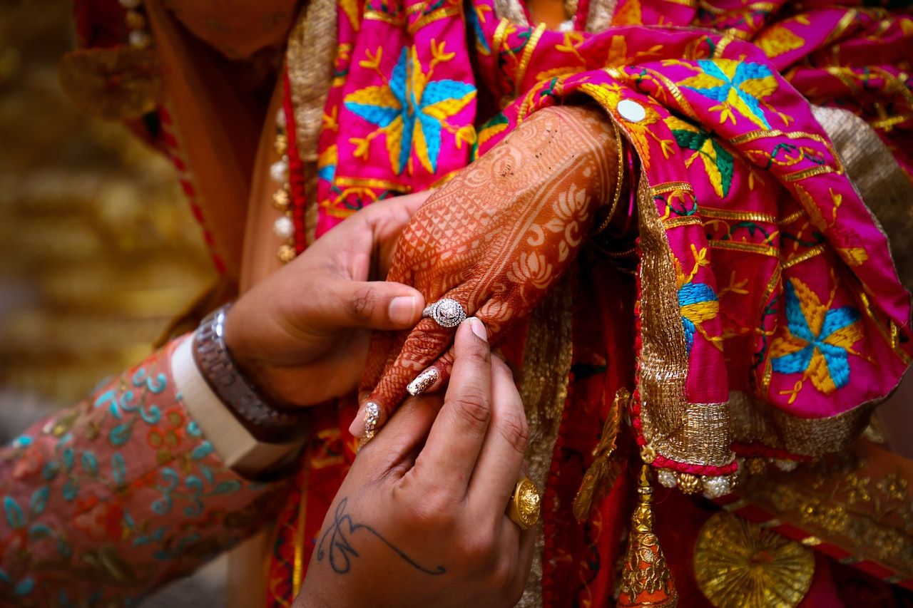 A man putting an engagement ring on a woman's hand