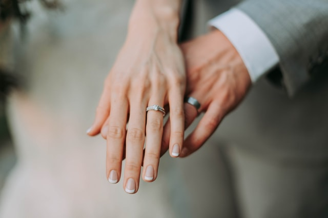 Hands of a just married couple with their wedding rings